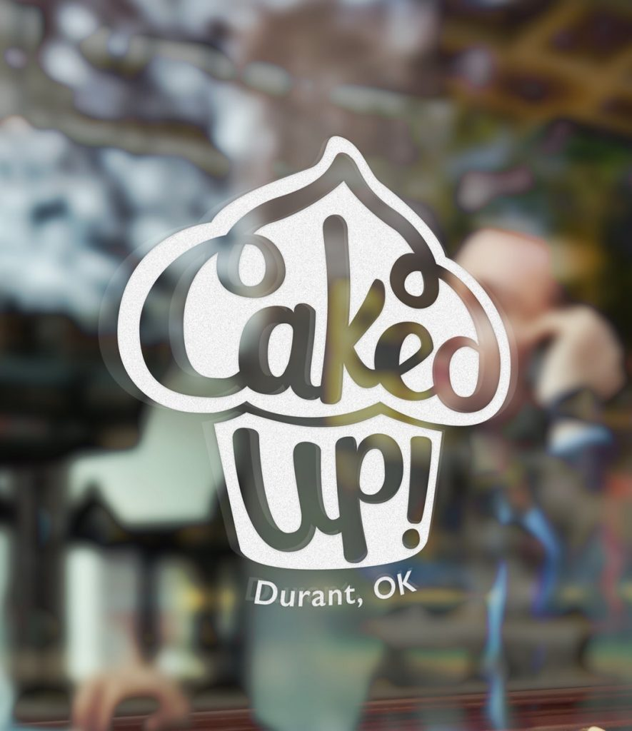 Logo for Caked Up! on a window